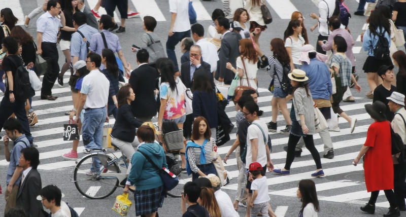 "People cross the street in Tokyo, Monday, July 1, 2013. Business sentiment among major Japanese manufacturers turned positive for the first time in nearly two years, a signal that companies are reacting positively to the weaker yen and Prime Minister Shinzo Abe's policies to revive the stagnant economy. The Bank of Japan's closely-watched quarterly ""tankan"" survey for June, announced Monday, showed that the index for major manufacturers rose to positive 4 from negative 8 in March. (AP Photo/Koji Sasahara)"