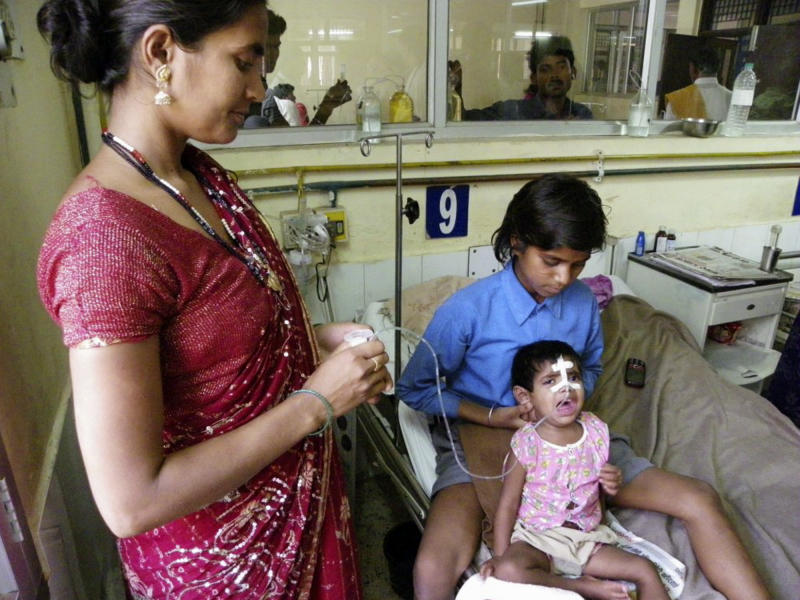 In this Tuesday, April 2, 2013 photo, an Indian child in a pink shirt undergoes treatment for encephalitis at a hospital in Gorakhpur in Uttar Pradesh state, India. Encephalitis is sweeping through northern India, killing at least 118 children in what officials worry could become the deadliest outbreak in nearly a decade. (AP Photo/Biswajeet Banerjee)