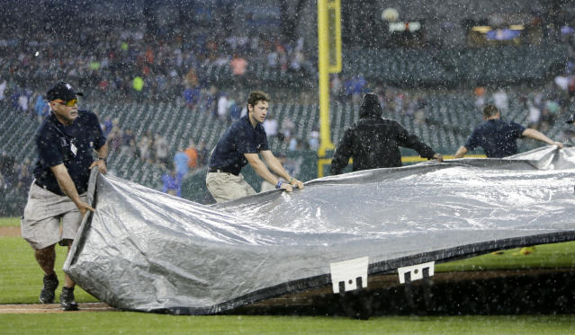 Detroit Tigers' grounds crew work to cover the field during a thunderstorm during the fourth inning of a baseball game against the Toronto Blue Jays, Saturday, July 20, 2019, in Detroit. (AP Photo/Duane Burleson)