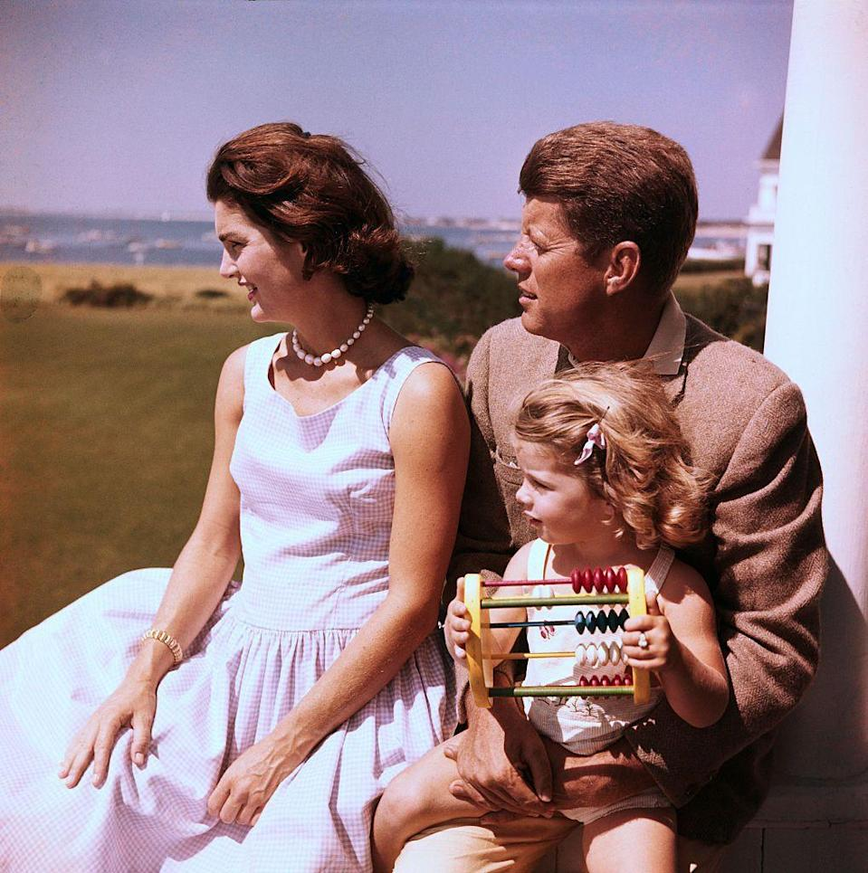 <p>Jackie, dressed for summer in a gingham print dress and pearls, relaxes with husband JFK and daughter Caroline. </p>