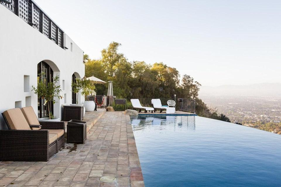 "It's hard to beat an infinity pool, especially one that looks out over <a href=""https://www.cntraveler.com/destinations/los-angeles?mbid=synd_yahoo_rss"" rel=""nofollow noopener"" target=""_blank"" data-ylk=""slk:Los Angeles"" class=""link rapid-noclick-resp"">Los Angeles</a>. Combined with the hot tub, sun loungers, BBQ grill, and full-size bar, this backyard has everything you need for long, leisurely afternoons outdoors. The inside of this four-bedroom home is worthy of a stay itself, too, though with a massive kitchen and another bar; a big, airy living room; a spa-like soaking tub; and king beds in every room. $1499, Airbnb (starting price). <a href=""https://www.airbnb.com/rooms/plus/20541631"" rel=""nofollow noopener"" target=""_blank"" data-ylk=""slk:Get it now!"" class=""link rapid-noclick-resp"">Get it now!</a>"