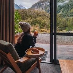 Woman sitting in a cozy lodge with drink in hand, looking out at the mountains in Fiordlands National Park.