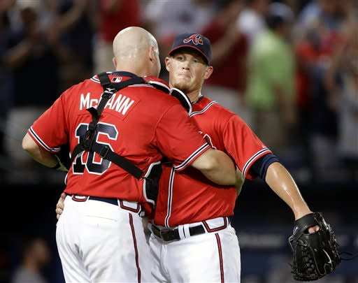 Atlanta Braves relief pitcher Craig Kimbrel, right, embraces teammate Brian McCann after closing out the ninth inning of a baseball game against the Arizona Diamondbacks, Friday, June 28, 2013, in Atlanta. The Braves beat the Diamondbacks 3-0. (AP Photo/David Goldman)