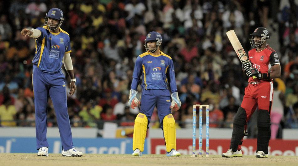 BRIDGETOWN, BARBADOS - AUGUST 3:  Captain Kieron Pollard (L) of Barbados Tridents sets the field for Trinidad & Tobago Red Steel Captain Dwayne Bravo (R) as keeper Umar Akmal (C) looks on during the Fifth Match of the Caribbean Premier League between Barbados Tridents v Trinidad & Tobago Red Steel at Kensington Oval on August 3, 2013 in Bridgetown, Barbados. (Photo by Randy Brooks/Getty Images Latin America for CPL)