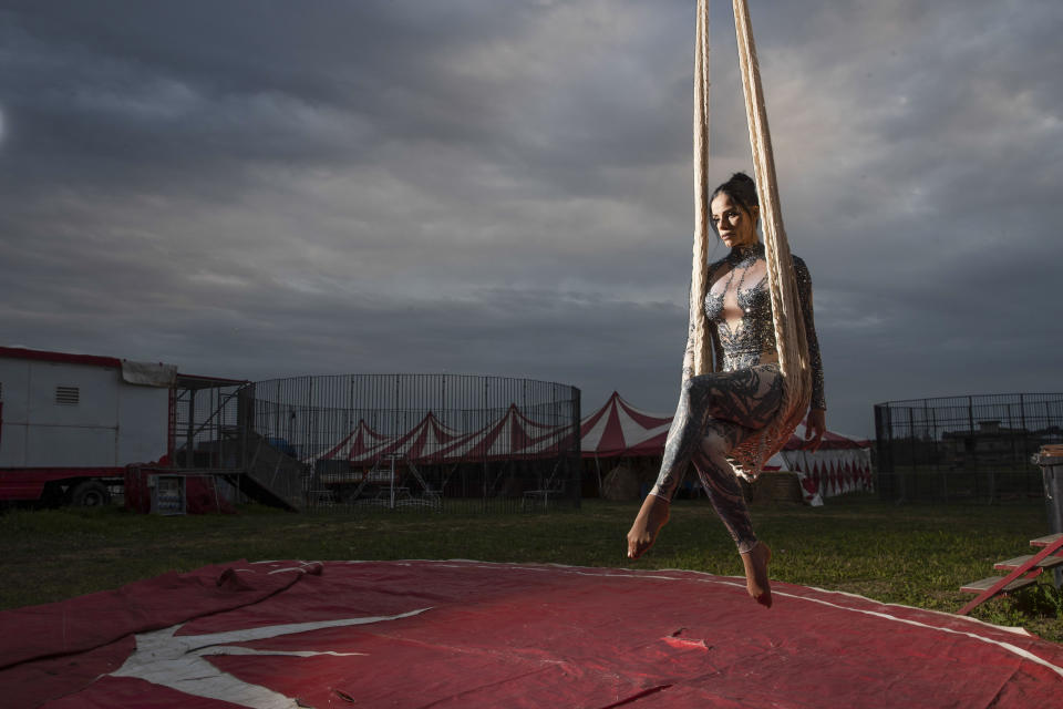 """Otilia Maria Martinez Dos Santos, an artist of Portuguese origin, poses for a portrait at the Rony Roller circus, parked in the outskirts of Rome, Saturday, April 18, 2020. Photographer Alessandra Tarantino said she came up with the idea to shoot circus workers after growing frustrated and bored with the postcard-like shots of an empty Rome during lockdown. The shot was taken between poses, with the swing seemingly attached to the sky. """"Her empty gaze, lost in the void, deeply affected me. It's hard to dance without the music,"""" Tarantino said. (AP Photo/Alessandra Tarantino)"""