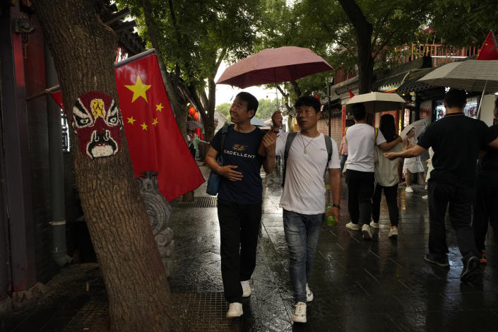 """Visitors pass through the popular Nanluoguxiang alley way in Beijing on Saturday, July 3, 2021. A small but visible handful of urban Chinese are rattling the ruling Communist Party by choosing to """"lie flat,"""" or reject high-status careers, long work hours and expensive cities for a """"low-desire life."""" That clashes with party ambitions to make China a wealthier consumer society. (AP Photo/Ng Han Guan)"""