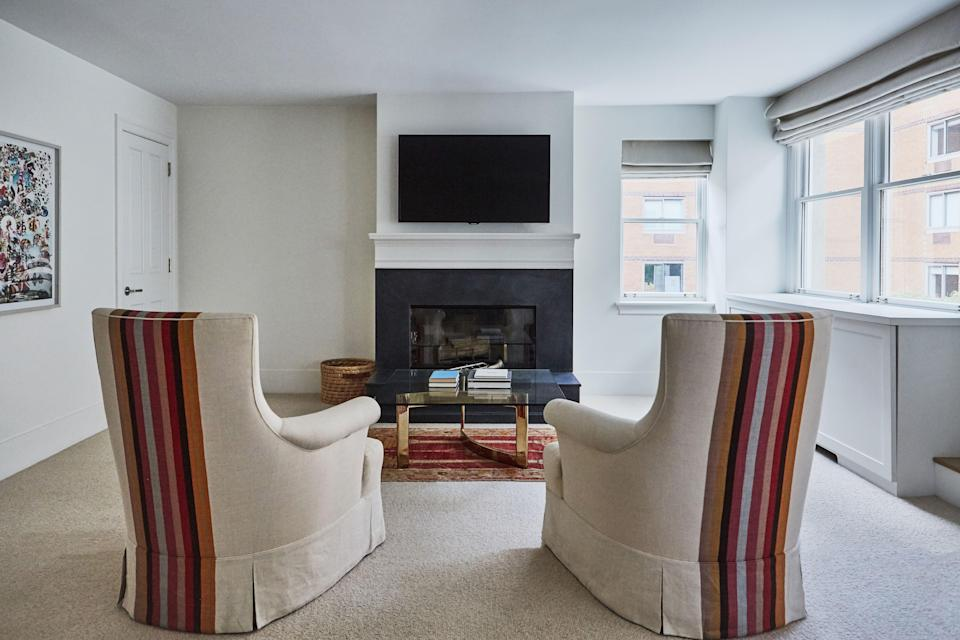 Though the upholstered chairs may be the highlight of this sitting area, other details are not to be missed: The coffee table is a mid-century find and the rug was purchased through Bonhams. The fireplace was redone with black slate.