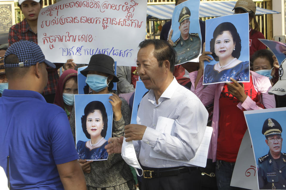 Rong Chhun, center, president of the Cambodian Confederation of Unions talks with a security, left, during a protest near the prime minister's residence in Phnom Penh, Cambodia July 29, 2020. Rong Chhun was arrested Friday night, July 31 on a charge of inciting social unrest because of his comments about a politically sensitive matter concerning the country's borders. (AP Photo/Heng Sinith)
