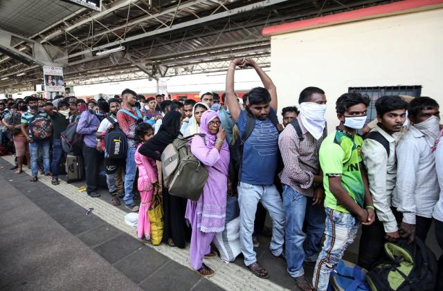 Migrant workers and their families queue to board a train at a railway station, after government imposed restrictions on public gatherings in attempts to prevent spread of coronavirus disease (COVID-19), in Mumbai, India, March 21, 2020. REUTERS/Prashant Waydande