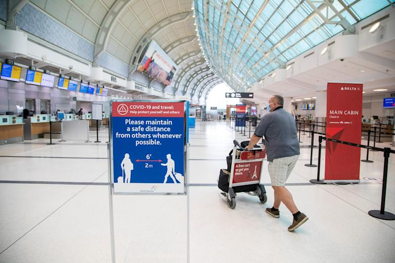 "A man pushes a baggage cart wearing a mandatory face mask as a ""Healthy Airport"" initiative is launched for travel, taking into account social distancing protocols to slow the spread of the coronavirus disease (COVID-19) at Toronto Pearson International Airport in Toronto, Ontario, Canada June 23, 2020. REUTERS/Carlos Osorio"