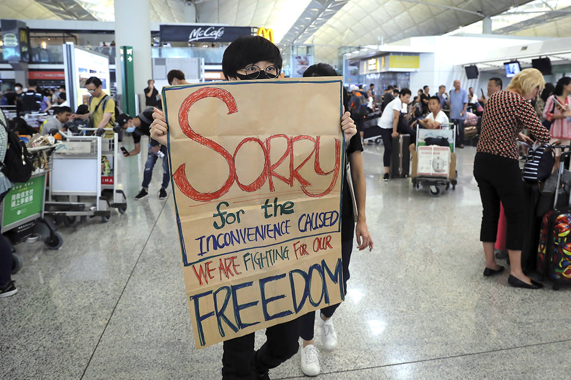 A protester shows a placard to stranded travelers during a demonstration at the Airport in Hong Kong, Tuesday, Aug. 13, 2019. Protesters severely crippled operations at Hong Kong's international airport for a second day Tuesday, forcing authorities to cancel all remaining flights out of the city after demonstrators took over the terminals as part of their push for democratic reforms.