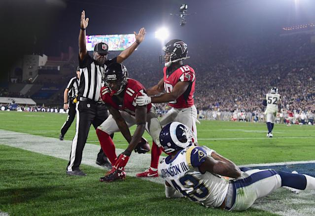 <p>Wide receiver Julio Jones #11 of the Atlanta Falcons makes a touchdown catch in front of strong safety John Johnson #43 of the Los Angeles Rams as wide receiver Taylor Gabriel #18 celebrates during the fourth quarter of the NFC Wild Card Playoff game at Los Angeles Coliseum on January 6, 2018 in Los Angeles, California. (Photo by Harry How/Getty Images) </p>