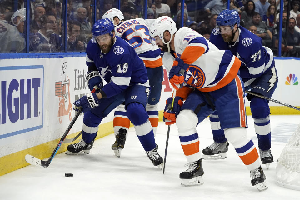 Tampa Bay Lightning center Barclay Goodrow (19) moves the puck past New York Islanders center Casey Cizikas (53) and right wing Cal Clutterbuck, front right, during the third period in Game 7 of an NHL hockey Stanley Cup semifinal playoff series Friday, June 25, 2021, in Tampa, Fla. (AP Photo/Chris O'Meara)