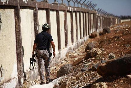 A Free Syrian Army fighter carries his weapon as he walks along the fence of the Menagh airport which, according to the FSA, is partially controlled by Syrian regime forces in Aleppo's countryside
