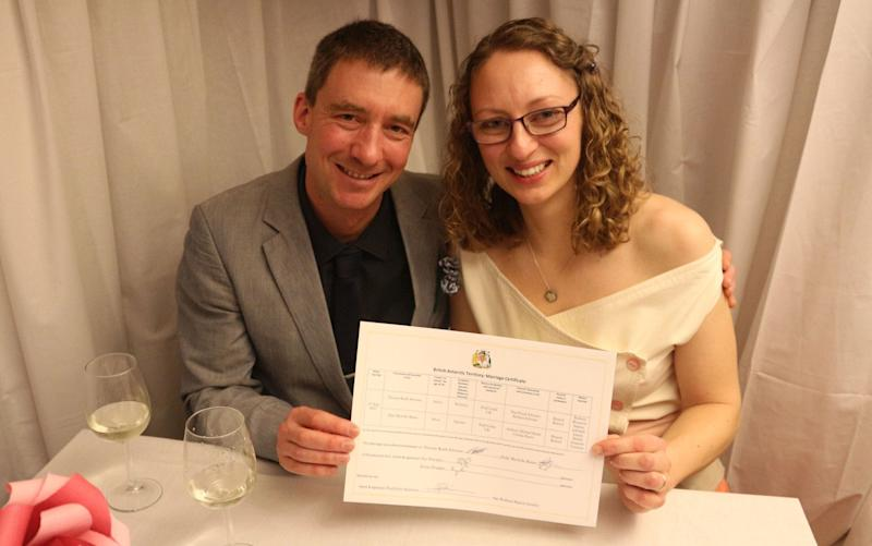 Julie Baum and Tom Sylvester hold their marriage certificate - Credit: British Antarctic Survey/PA