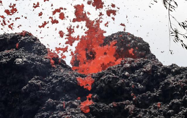 <p>A lava fissure erupts in the aftermath of eruptions from the Kilauea volcano on Hawaii's Big Island, on May 12, 2018 in Pahoa, Hawaii. (Photo: Mario Tama/Getty Images) </p>