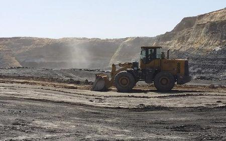 A mine worker drives a shovel truck across an open-cast coal mine located in the Ordos mining district