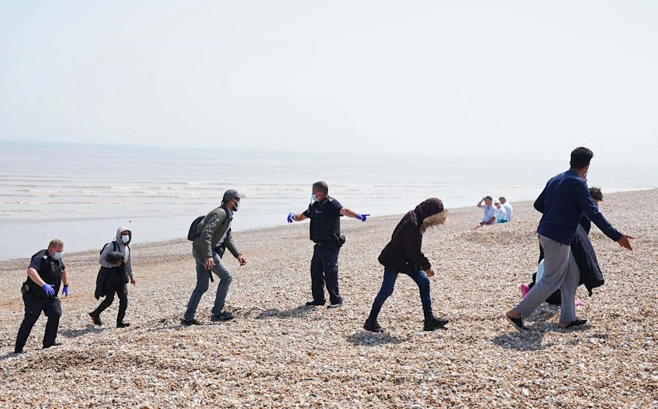 People are escorted from the beach in Dungeness, Kent (Gareth Fuller/PA) (PA Wire)