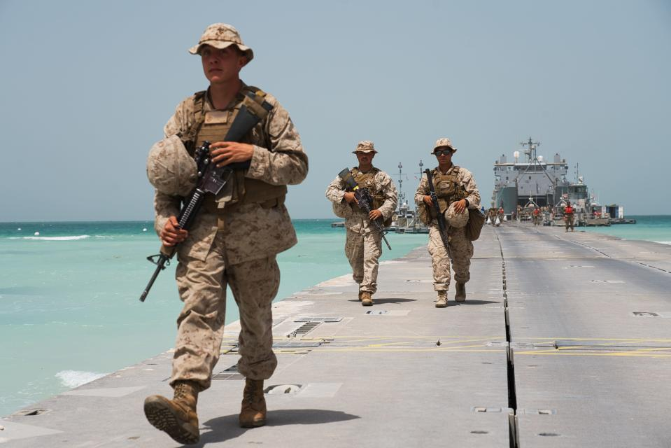 U.S. Marines walk down a removable Trident Pier leading to an American ship docked near an Emirati military base home to a Military Operations and Urban Terrain facility in al-Hamra, United Arab Emirates, Monday, March 23, 2020. U.S. Marines and Emirati forces held the biennial exercise, called Native Fury, that saw forces seize a sprawling model Mideast city. The drill on Monday was conducted amid tensions with Iran and despite the global new coronavirus pandemic. (AP Photo/Jon Gambrell)