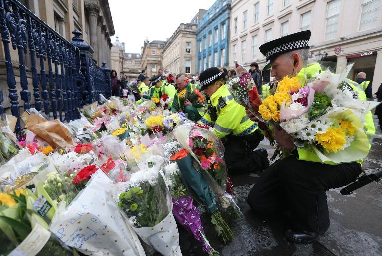 Police officers arrange floral tributes left by members of the public for victims of a refuse truck accident in Glasgow, on December 23, 2014