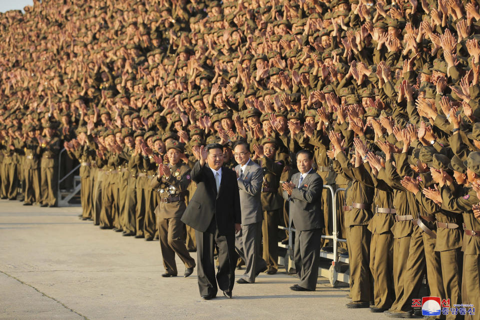 """In this photo provided by the North Korean government, North Korean leader Kim Jong Un, center, waves to participants as they gather for a group photo, in a celebration of the nation's 73rd anniversary at Kim Il Sung Square in Pyongyang, North Korea, Thursday, Sept. 9, 2021. Independent journalists were not given access to cover the event depicted in this image distributed by the North Korean government. The content of this image is as provided and cannot be independently verified. Korean language watermark on image as provided by source reads: """"KCNA"""" which is the abbreviation for Korean Central News Agency. (Korean Central News Agency/Korea News Service via AP)"""