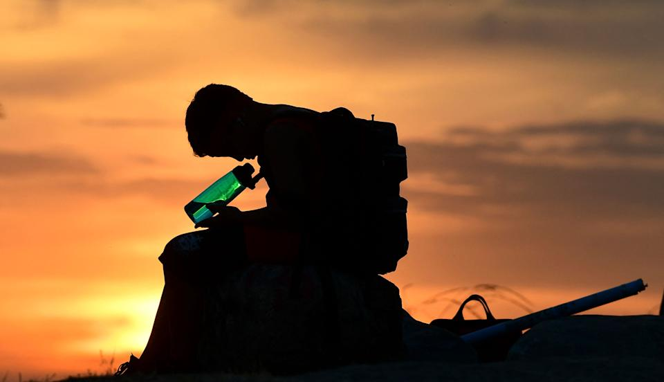 A child looks at his water bottle as the sun sets on June 15, 2021 in Los Angeles, California as temperatures soar in an early-season heatwave. (Frederic J. Brown/AFP via Getty Images)