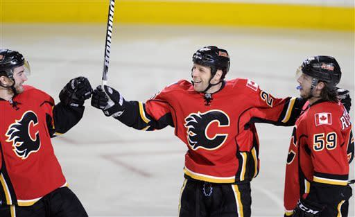 Calgary Flames' Steve Begin, center, celebrates a third period goal against the Detroit Red Wings with TJ Brodie, left, and Max Reinhart during NHL action in Calgary, Alberta, Wednesday, April 17, 2013. (AP Photo/The Canadian Press, Larry MacDougal)