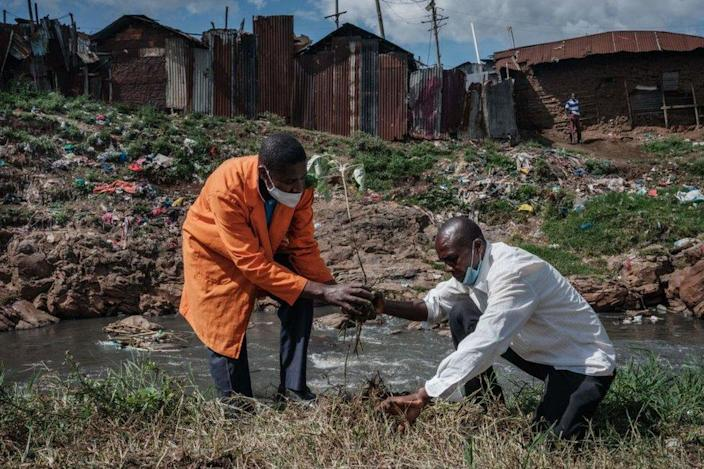Two men plant a tree on a littered riverbank.