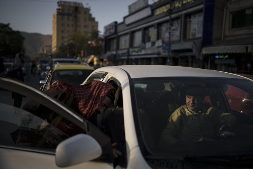 An afghan man watches as a Taliban fighter searches his car at a checkpoint in Kabul, Afghanistan, Tuesday, Sept. 14, 2021. It is a symbol of the moment of transition they find themselves in: Once warriors embedded in Afghanistan's rugged mountains, now the Taliban are an urban police force. (AP Photo/Felipe Dana)