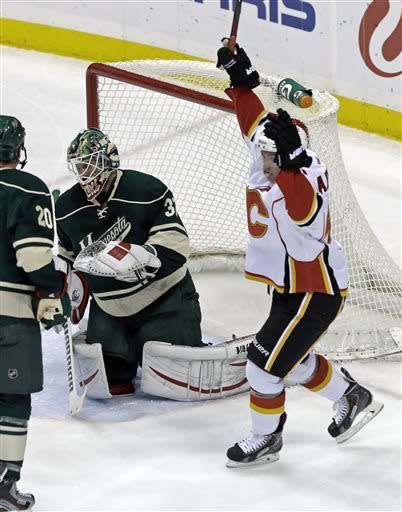 Calgary Flames' Sven Baertschi, right, of Switzerland, celebrates a power-play goal by teammate Mark Cundani in the first period of an NHL hockey game off Minnesota Wild goalie Niklas Backstrom, center, of Finland, Sunday, April 21, 2013, in St. Paul, Minn. (AP Photo/Jim Mone)