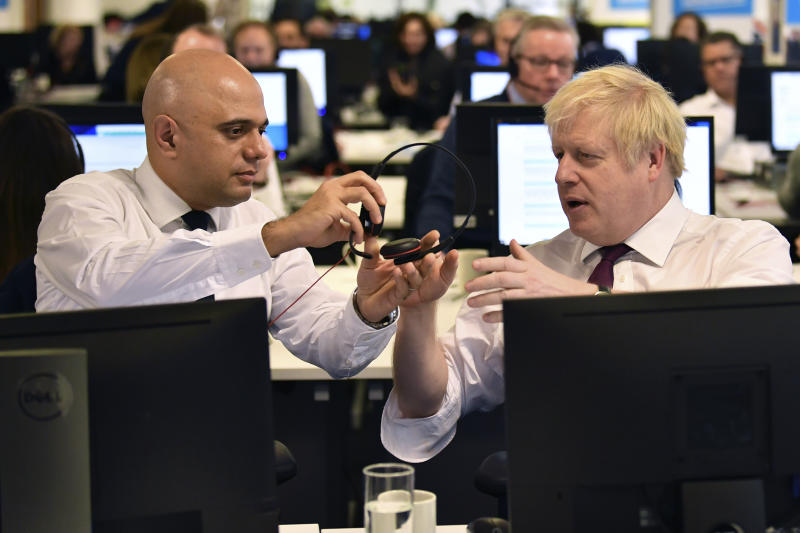 Britain's Prime Minister Boris Johnson, right and Chancellor of the Exchequer Sajid Javid exchange headsets, at the Conservative Campaign Headquarters Call Centre, while on the General Election trail, in central London, Sunday, Dec. 8, 2019. Britain goes to the polls on Dec. 12. (Ben Stansall/Pool Photo via AP)