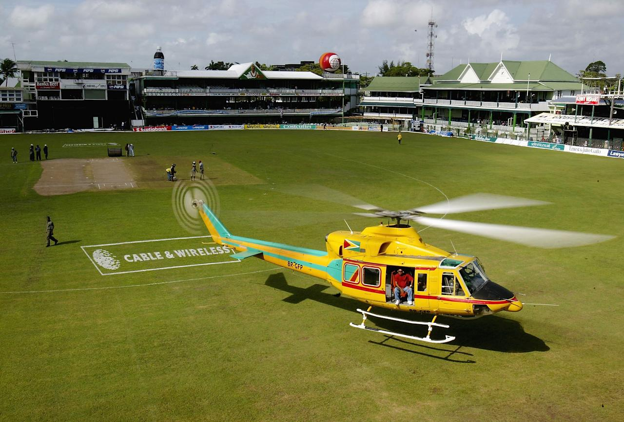 GEORGETOWN, GUYANA - APRIL 18:  A helicopter hovers just above the ground in an attempt to dry out the pitch to make play possible at the Border Ground, on April 18, 2004, in Georgetown, Guyana. (Photo by Tom Shaw/Getty Images)
