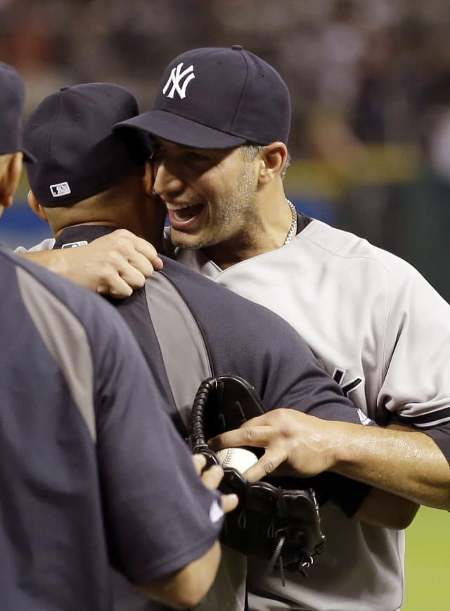 New York Yankees starting pitcher Andy Pettitte, right, hugs Mariano Rivera, left, after pitching a complete baseball game against the Houston Astros Saturday, Sept. 28, 2013, in Houston. The Yankees beat the Astros 2-1. Pettitte is retiring at the end of the season.(AP Photo/David J. Phillip)