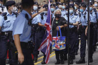 A protester holding a U.K. flag is arrested by police officers during the 24th anniversary of Hong Kong handover to China at a street in Hong Kong Thursday, July 1, 2021. (AP Photo)