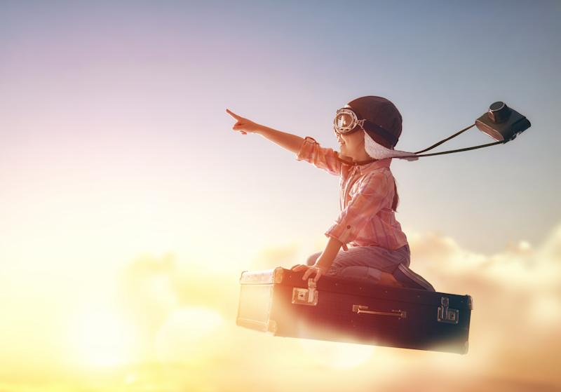 A child in aviator gear with a camera swinging from his neck sitting on a suitcase that's flying high into the clouds.