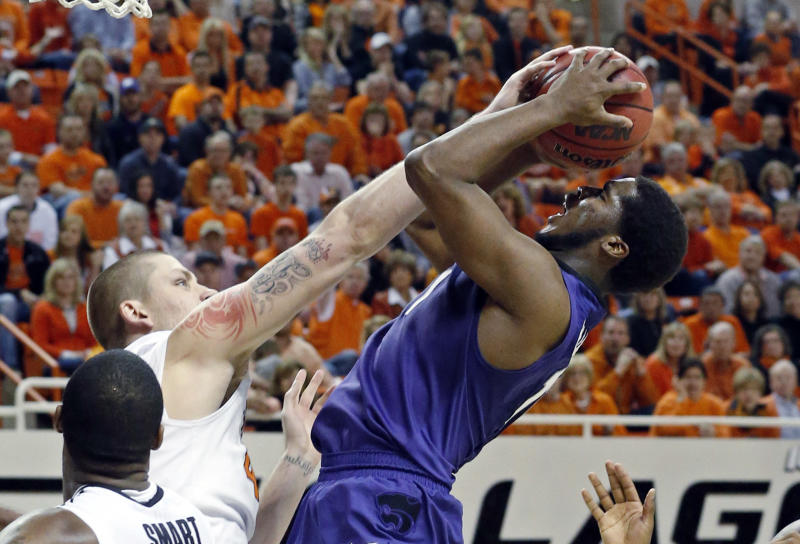 Oklahoma State forward Philip Jurick, left, fouls Kansas State forward Nino Williams as he shoots in the second half of an NCAA college basketball game in Stillwater, Okla., Saturday, March 9, 2013. Oklahoma State won 76-70. (AP Photo/Sue Ogrocki)