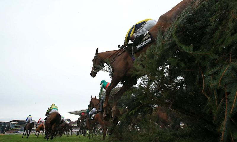 The Grand National field jump a fence at Aintree during the 2016 race.