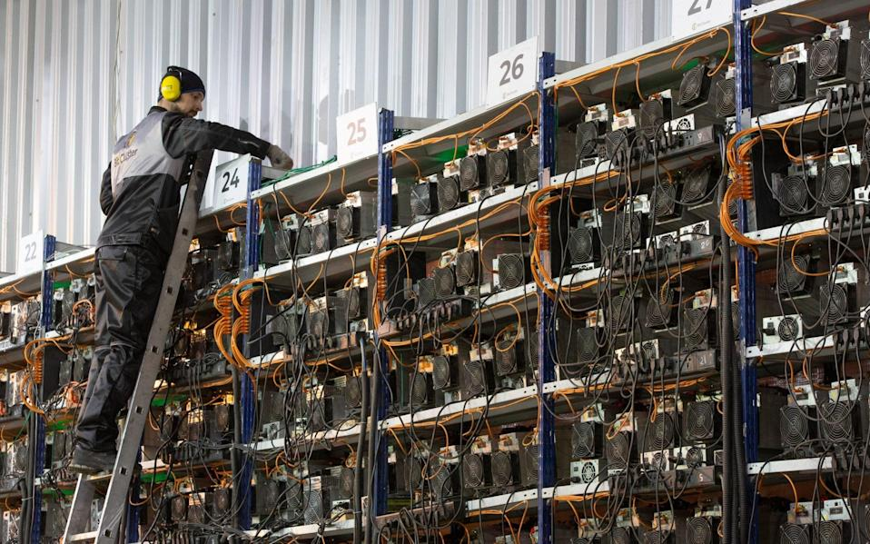 An engineer on a ladder inspects racks of application-specific integrated circuit (ASIC) mining devices and power units at the BitCluster cryptocurrency mining farm in Norilsk, Russia - Andrey Rudakov/Bloomberg