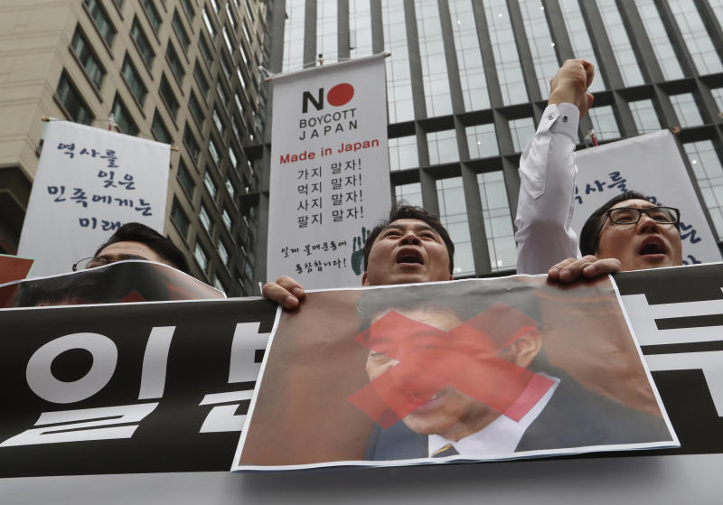 """South Korean small and medium-sized business owners with a defaced image of Japanese Prime Minister Shinzo Abe shout slogans during a rally calling for boycott of Japanese products in front of the Japanese embassy in Seoul, South Korea, Monday, July 15, 2019. South Korea and Japan last Friday, July 12, failed to immediately resolve their dispute over Japanese export restrictions that could hurt South Korean technology companies, as Seoul called for an investigation by the United Nations or another international body. The signs read: """"We don't sell Japanese products."""" (AP Photo/Ahn Young-joon)"""