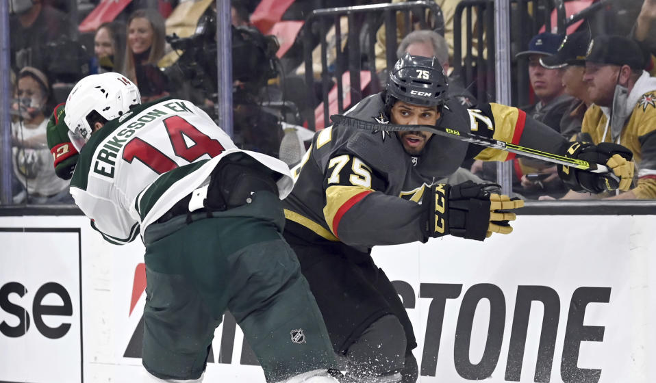 Minnesota Wild center Joel Eriksson Ek (14) defends against Vegas Golden Knights right wing Ryan Reaves (75) during the second period of Game 1 of a first-round NHL hockey playoff series Sunday, May 16, 2021, in Las Vegas. (AP Photo/David Becker)