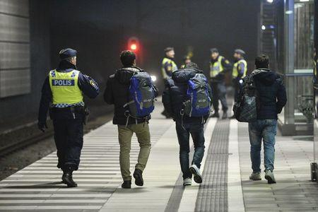 A police officer escorts migrants from a train at Hyllie station outside Malmo, Sweden, in this November 19, 2015 file photo. REUTERS/Johan Nilsson/TT NEWS AGENCY/Files