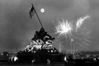 FILE - In this July 4, 1966 file photo, the moon shines above the United States Marine Corps War Memorial, which depicts a scene from Iwo Jima, as fireworks burst over Washington, seen from the Virginia side of the Potomac River. The Washington Monument and the Lincoln Memorial are seen in the background. (AP Photo/Charles Tasnadi, File)