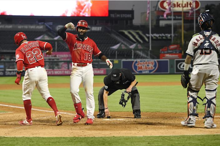 """Angels outfielder Brian Goodwin, second from left, celebrates after hitting a two-run home run during the fourth inning of a game against the Astros at Angel Stadium. <span class=""""copyright"""">(Mark J. Terrill / Associated Press)</span>"""