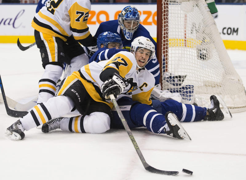 Pittsburgh Penguins center Sidney Crosby (87) battles for the puck as Toronto Maple Leafs goaltender Frederik Andersen (31) and defenseman Jake Muzzin, center, watch during the third period of an NHL hockey game Thursday, Feb. 20, 2020, in Toronto. (Nathan Denette/The Canadian Press via AP)