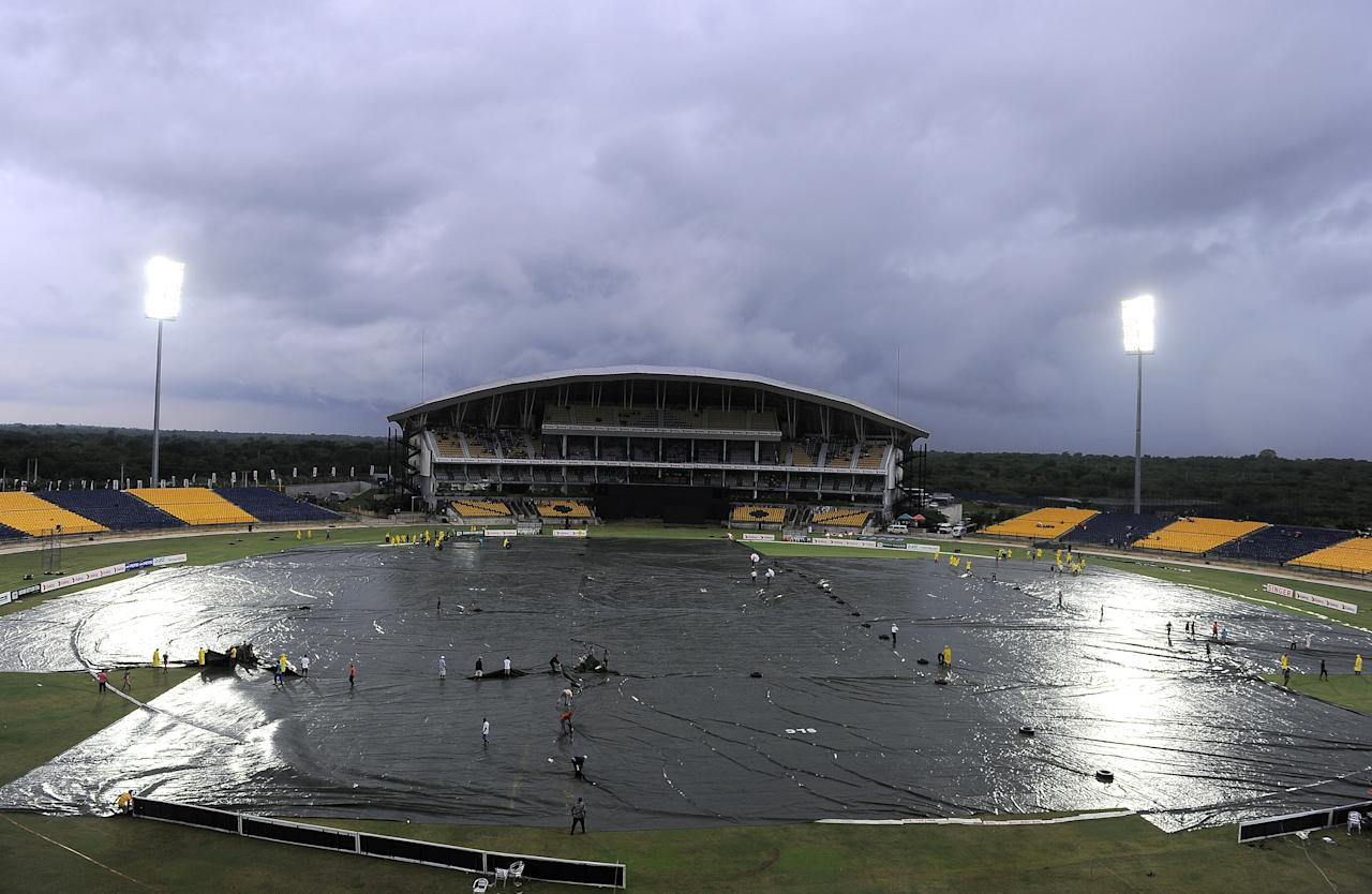 Sri Lankan groundstaff cover the ground with tarpaulins as rain stops play during the second One Day International (ODI) cricket match between Sri Lanka and New Zealand at the Suriyawewa Mahinda Rajapakse International Cricket Stadium in the southern district of Hambantota on November 12, 2013. AFP PHOTO/ LAKRUWAN WANNIARACHCHI        (Photo credit should read LAKRUWAN WANNIARACHCHI/AFP/Getty Images)