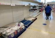 FILE PHOTO: A shopper pushes her trolley along an almost empty toilet paper aisle in a Tesco supermarket following the outbreak of the coronavirus disease (COVID-19) in Manchester, Britain