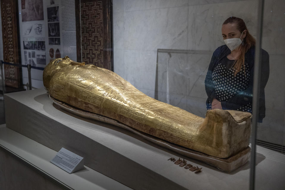 FILE - In this April 24, 2021 file photo, a woman looks at a golden sarcophagus on display at the National Museum of Egyptian Civilization in Old Cairo. As some European countries re-open to international tourists, Egypt has already been trying for months to attract them to its archaeological sites and museums. Officials are betting that the new ancient discoveries will set it apart on the mid- and post-pandemic tourism market (AP Photo/Nariman El-Mofty, File)