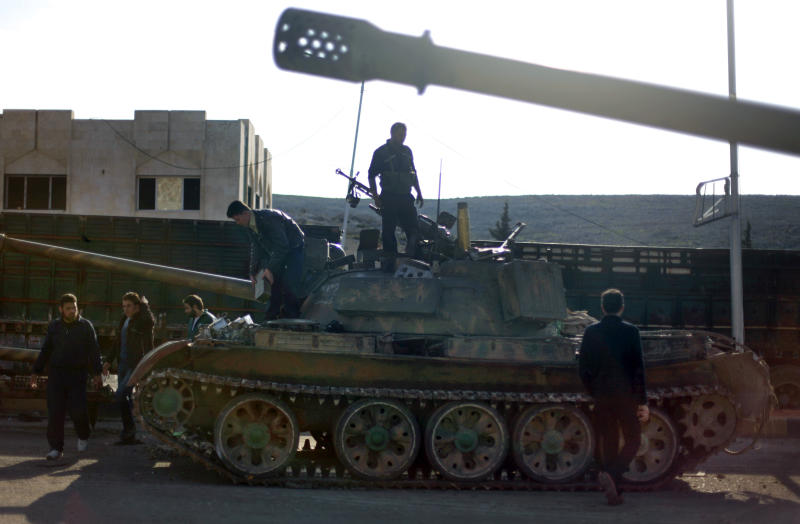 Syrian fighters check a tank they took after storming a military base in Aleppo, Monday, Nov. 19, 2012. (AP Photo/ Khalil Hamra)