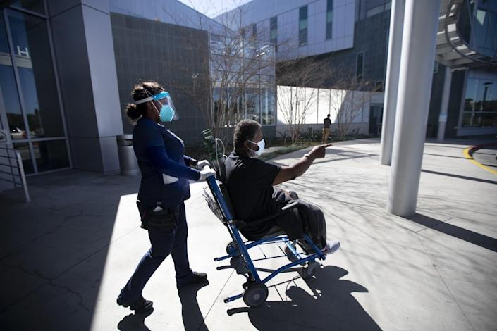 Richard Perry points as he's pushed in a wheelchair.