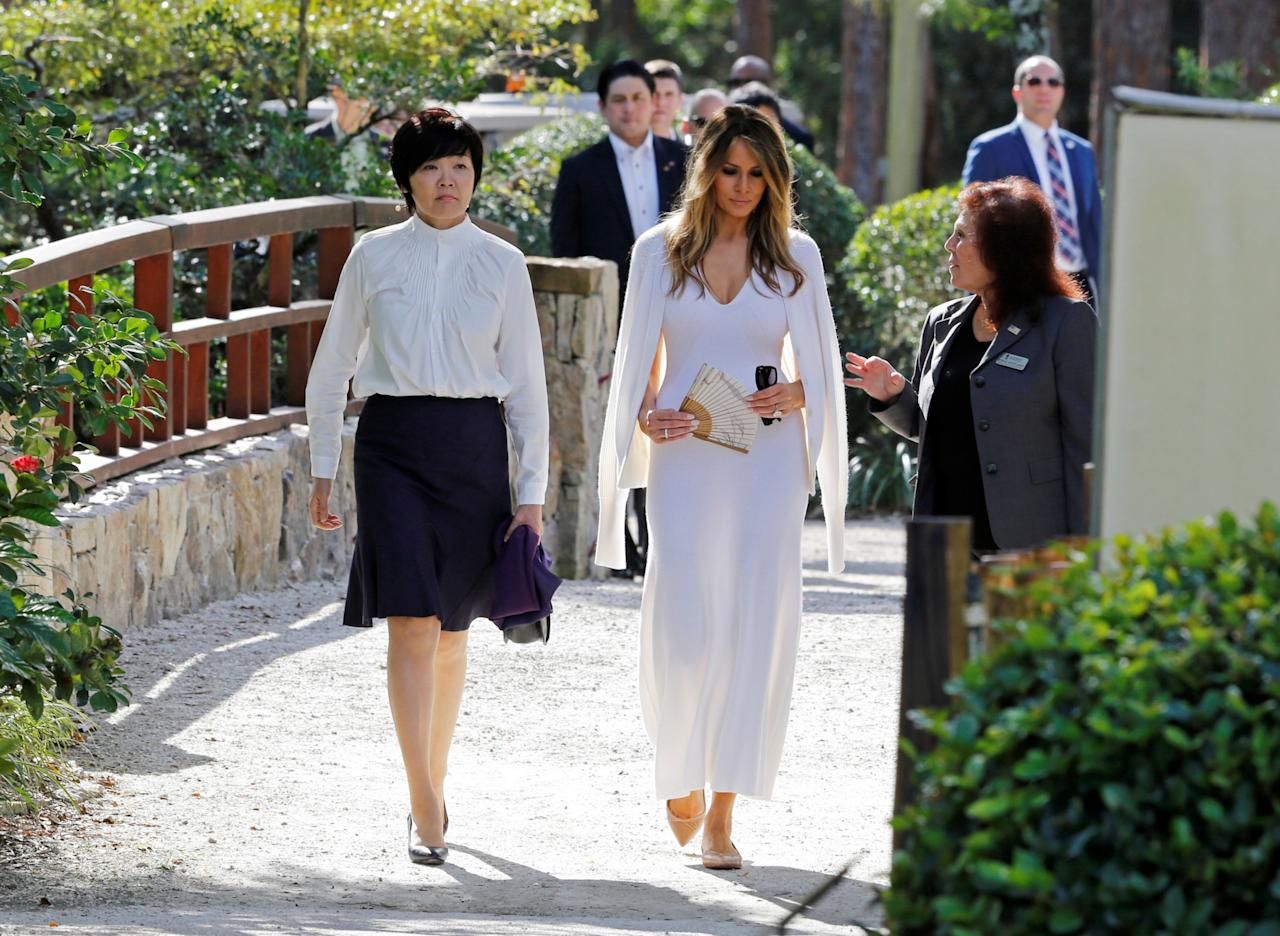 """<p>To tour the Morikami Museum and Japanese Gardens while hosting Japanese Prime Minister Shinzo Abe and his wife Akie Abe, Melania Trump chose a mid-calf length white dress with a matching cardigan from Calvin Klein (one of the few American designers who <a rel=""""nofollow"""">responded with a resounding yes</a> to dressing the first lady). (Photo: Reuters) </p>"""